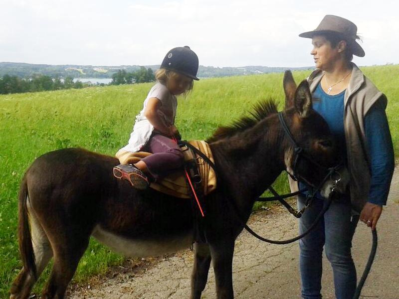 Kind reitet auf einem Esel unter Aufsicht eines Erwachsenen