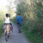 Kind reitet auf einem Esel, der von einem Erwachsenen geführt wird.
